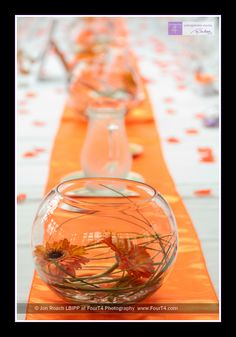 Bowls of gerberas as part of an orange-themed table setting for a New Forest wedding.