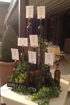 Wine bottle table seating plan. Using Italian wine bottles, wooden vintage wine crates, climbing ivy and grapes.