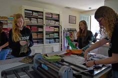 Mackenzie Murphy, 17, a Vanden High School senior (left) and Marilyn Lewis, area coordinator for the Vacaville Binky Patrol, (right) sort and cut donations of fabric. Murphy's mother Carla has donated her living room to the Binky Patrol's cause: comfortable quilts for children in crisis. Jessica Rogness — The Reporter