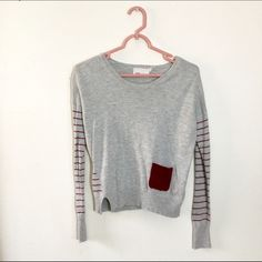 Anthropologie Yoon Assymetrical Sweater Yoon brand sweater from Anthropologie. This soft grey sweater features charming details such as maroon stripes on the sleeves, a maroon pocket on the front, and a slit and stripes on one side of the bottom hem. Size small. 45% viscose, 30% nylon, 20% cotton, 5% wool. Very minor pilling. Anthropologie Sweaters Crew & Scoop Necks