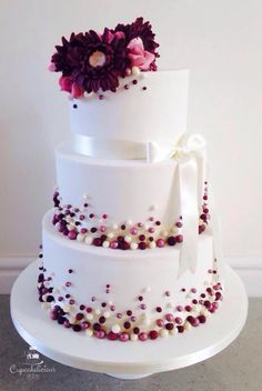 Super neat wedding cake with burgundy gerberas Daisy's, pink roses and matching…