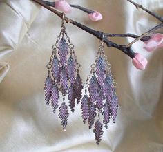 Peyote Stitched Dove Grande Chandeliers by mikelle77 on Etsy, $288.00--Made from miyuki delica glass seed beads, thread, pearl, sterling silver-- These beautiful beaded earrings conceal a hidden meteorite pearl drop accent visible only from the back or by a glimpse of motion. Hand-made sterling wire armature, chain, and sterling earwires for comfort and durability.  Measures approx 4 inches (10.5 cms) long; 1 1/2 inches (4 cms) wide at widest point.