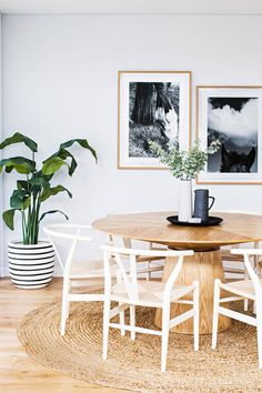 dining room with tan round woven rug, white wishbone chairs, light tan wood round dining table, indoor plant, striped pot, pantone warm sand, light tan, light beige