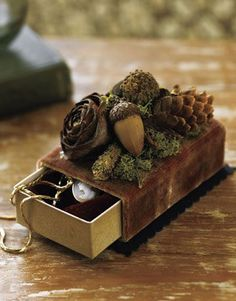 Nestle a vintage necklace or brooch in a simple slide jewelry box covered in rich velvet and topped with acorns, moss, and pine cones.