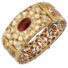 Indian Gold, Foiled-Back Garnet and Diamond, Enamel and Jaipur Enamel Bangle Bracelet The pierced tapered bangle centering one oval foiled-back garnet approximately 10.6 x 13.8 mm., surrounded by vari-shaped foiled-back table-cut diamonds, the reverse with an openwork floral motif applied with red, green, white and blue enamel, edged with table-cut diamonds within gold rectangles, the interior decorated with Jaipur enamel, approximately 31.3 dwts. Inner circle 6 3/4 inches.