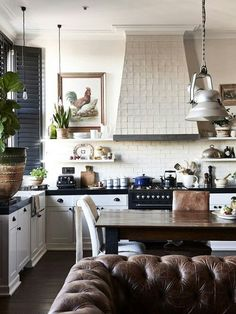 Ooooo.....love so much about this! The leather tufted sofa, the rooster art, the industrial lights, the tiled hood...and on and on.