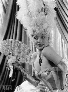 "Lucy and a fan  LIFE's Walter Sanders photographed Ball in costume for the extravagant dream sequence set in 18th-century France at the center of ""DuBarry Was a Lady."" In this 1943 adaptation of Cole Porter's Broadway hit, hoofer Ball had the lead role as a golddigging nightclub singer, opposite fellow comic Red Skelton and a rising song-and-dance man named Gene Kelly. She was billed in the movie's trailer as ""Queen of the Red-Heads."""