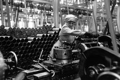 Circa 1915: A woman munitions worker operates a machine that makes shell cases in an armaments factory during the First World War