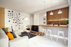 The first apartment  is a home in Warsaw. The look uses quite a bit of white from the walls to the lacquered metal barstools to the whitewashed floor, which serves to open up the space and bounce around plenty of natural light from the large windows.