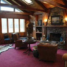 Fall and winter event guests can cozy up by a common area fire in the living room. #thekaaterskill