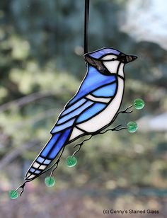 A stunning Blue Jay stained glass suncatcher for your home. This beautifully handcrafted suncatcher measures approximately 10 X 5. I added wire work including glass beads for berries and glass leaves on the wire branch. I take pride in my work to ensure you will be totally