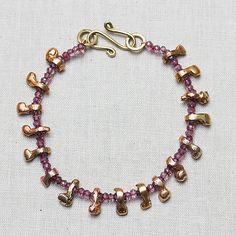 Beautiful, faceted, round, pink garnet and Moulay tribal African beads alternate on this bracelet for all seasons. Brass beads are handmade and irregular,making each piece of jewelry unique. You can war this piece alone or pair it with another piece to complete your look!