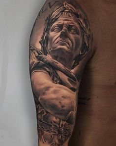 Black and grey Julius Caesar tattoo on the right upper arm.
