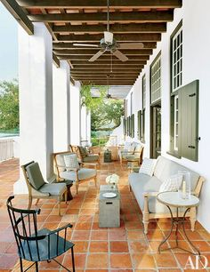 Reclaimed terra-cotta tile from François & Co. and teak seating add to the traditional feel of this lakeside Louisiana home, which was designed by McAlpine Tankersley Architecture and decorated by McAlpine Booth & Ferrier Interiors.