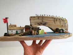 A one off original piece of driftwood art which would make a great gift. The bridge crosses the water to the little cottages. An old rusty boat is tied up waiting to be taken out.  I found the piece of wood that makes the bridge in Bolivia, the last photo shows where I found it, the Little Cottages, Little Houses, Salvaged Wood, Weathered Wood, Dorset Beaches, Seaside Decor, Wood Scraps, Driftwood Crafts, Wooden Ornaments