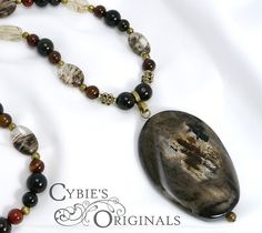 "Unique semi-precious silver leaf jasper pendant on a beaded strand of black and red agate with tourmilated and rutilate quartz accents.  Measures approximately 20"" in length."