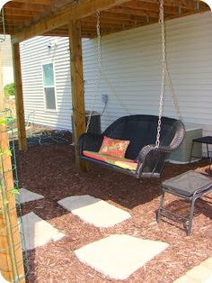 Patio under deck: porch swing, twinkle lights, table and potted plants, outdoor rug?