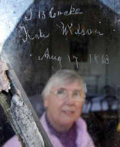 Sister Maureen Carroll, one of the nuns at Belmead on the James in Powhatan County, VA, looks up at the names J. B. Cocke and Kate Wilson with the date Aug. 17, 1863 carved with a diamond on one of the mansion's windowpanes. The names are those of the son of the original owner, Philip St. George Cocke, and his new bride on their wedding day. A small group of nuns are working to preserve the history and heritage of the ante-bellum mansion.