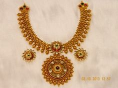 22 carat gold bridal necklace studded with kundans and rubies, teamed up with matching earrings by https://www.kotharijewelry.com/ Pune