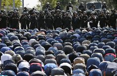 Palestinians pray as Israeli policemen stand guard during Friday prayers in the East Jerusalem neighbourhood of Wadi al-Joz October 10, 2014. Israeli police declared an age limit on Friday for Palestinians wanting to enter the Old City, only allowing males above the age of 50 and all females to enter. (REUTERS/Ammar Awad)