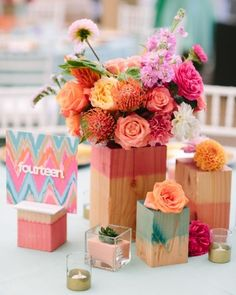 "This would look so cute as the center pieces for mops! ""Painted wood cubes held a mix of protea, roses, carnations, dahlias, and pink stock. On some tables, glass votive holders were spiced up with gold paint at the bases, and square prints of the same ikat from the invite showcased table numbers cut out of Plexiglas."""