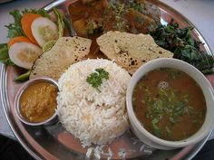"""Nepalese food - The most popular food and national dish is """"Dhal Bhat"""", which you will encounter daily during teahouse treks. Nepalese people eat it twice a day, for both of their main meals. It comes in different varieties: Dhal is a lentil soup and Bhat means rice, but usually it is accompanied by several other vegetable dishes, such as curried vegetables, and pickles."""