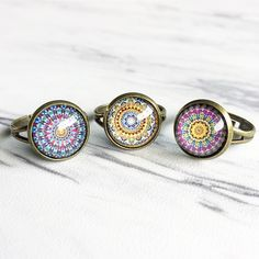 """Multi colored resin boho pattern ringS. The bronze colored base is nickel  free and made from brass. This adjustable ring changes to fit any size  finger with ease.  Stone size: 1/2"""""""