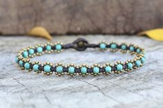 Very cute anklet clusters of 2.5mm brass beads and 4mm turquoise beads look like a flower woven together with dark brown wax cord and brass bell for