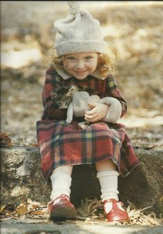 "Awww... She's so happy! She has a little, sweet kitten in her lap. Love the red tartan dress, gray knit hat, and old fashioned, ""Buster Brown"" T-strap shoes. Great photo!"