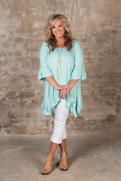 The Adley Basic Tunic is a jersey knit tunic has a scoop neckline, 3/4 bell sleeve with double ruffle detail and asymmetrical hem with ruffle detail.