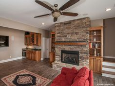 Walkout basement rec room with stone fireplace, built-ins, wet bar, and a red sofa that adds a pop of color! http://www.dongardner.com/plan_details.aspx?pid=4450. #Walkout #Basement #RecRoom