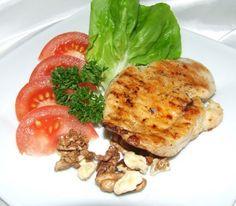 Grillowana w marynacie pierś z kurczaka z sałatą, pomidorem i orzechami.