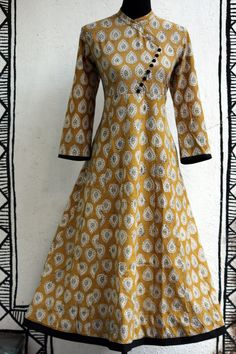 a long traditional anarkali with cross button potlis in angrakha style, inspired by mughal folklore. the leaf yellow anarkali with handblock print of leaves a
