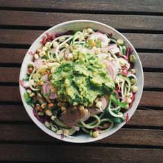 High-protein raw vegan salad: spinach, kale, spiralised zucchini, red onion, raw sprouted mung beans, chickpeas and lentils, red cabbage, topped with raw avocado/basil/garlic/lemon/hempseed pesto and drizzled with lemon juice.