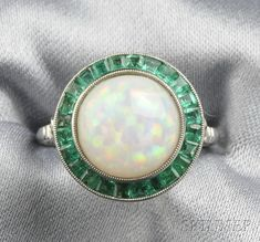 Platinum, Opal, and Emerald Ring, set with a cabochon opal measuring approx. 10.50 mm, framed by fancy-cut emeralds, millegrain accents, size 7.
