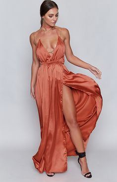 Allow your urban goddess to emerge amongst the inner city decay (hunger games style) in the Pandora Dress Rust. Be the girl on fire in stunning auburn rust satin that falls beautifully on the body. Featuring a bold low cut front, held up halter style with luxuriously long ties that fall over a bare back - but these ties allow you to express yourself however you feel, get creative and experiment with different back styles for every occasion. The maxi skirt falls from under the bust to the…