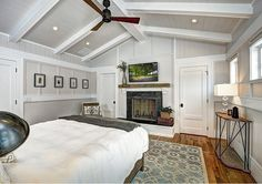 Bedroom Fireplace. Beach house bedroom. Beadboard Bedroom. Board and batten. Corbels. Grey walls. High windows. Master bedroom. Reclaimed wood mantel. Shiplap. Tongue and groove. White beam. White doors. White trim. Wood walls