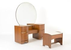A Mid Century Modern walnut dresser.  The dresser is designed with a round beveled glass mirror over a low vanity that features a center shelf with curved drawer and half glass shelf under mirror. ...