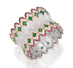 Set with 36 round emeralds weighing approximately 9.00 carats, bordered by numerous round rubies weighing approximately 4.50 carats, gross weight approximately 46 dwts, internal circumference 6 3/8 inches, signed Buccellati