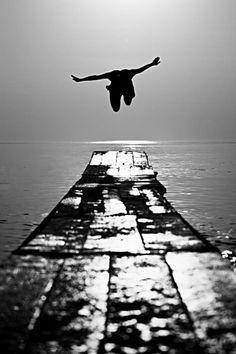 photo femme noir et blanc, homme qui du quai saute dans la mer, bras grands ouverts comme pour un vol dans le vide