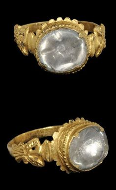 Post Medieval Spanish Doublet Sapphire Ring 16th century AD . A gold finger ring with flat-section hoop rising to flared shoulders with spread eagle detailing; the bezel discoid with raised cell, ropework detailing to the wall, a translucent doublet sapphire in a claw setting to the upper face.