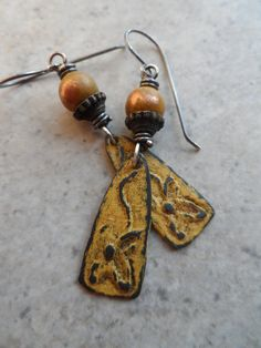 Gorgeous pewter charms finished in a golden/ochre matte color, expertly handcrafted by an etsy artisan, are wirewrapped with solid sterling silver (925) wire to aged copper beads, as well as pewter bead caps. Suspended from handcrafted solid sterling silver earwires, these earrings measure about 2 1/4 from end to end. You are going to love these