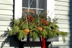 Interested in classy Christmas decorations? This holiday window box incorporates not only greens but also berries, ornamental twigs, and even dried hydrangea heads. Browse my pictures here for more ideas: http://landscaping.about.com/od/winterlandscaping/ss/16-Ideas-for-Tasteful-Christmas-Yard-Decorations.htm