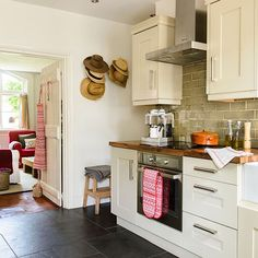 Slate floor and cream kitchen  Cream kitchen cabinetry and slate floor tiles in a variety of sizes give this country kitchen a rustic edge.