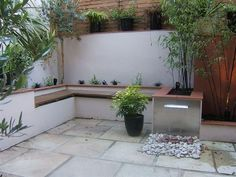 Integrated seating saves space & does away with the necessity for furniture which could clutter the space. This tiny garden even has a water feature. And restricted planting space doesn't mean there can't be plenty of plants!