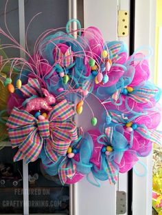 This beautiful Easter wreath was made by Terrie Dollar who sells her wreaths here. You will need… Wire wreath Pink and blue deco mesh Decorations (eggs, bunnies, bows, etc.) Hot glue gun Wire/pipe cleaners She said she just followed the directions in the YouTube video below and added two colors of deco mesh! Then hot …