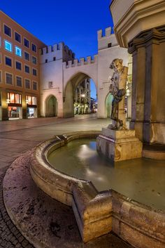 Brunnenbuberl Fountain And Karlstor Gate In The Evening | Munich | Germany | Photo By Andrey Omelyanchuk