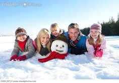 Portrait of smiling family laying in snow with snowman's head