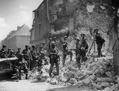 Paratroopers of the 101st Airborne standing on the ruins of a house after the Battle of Carentan.