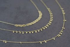 "Sia Taylor ""Grasses & Seeds"" gold necklaces."